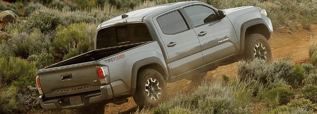 Rear passenger angle of a grey 2021 Toyota Tacoma driving off-road