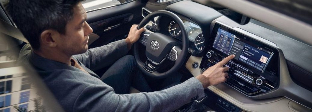 Man using the touchscreen inside the 2021 Toyota Highlander