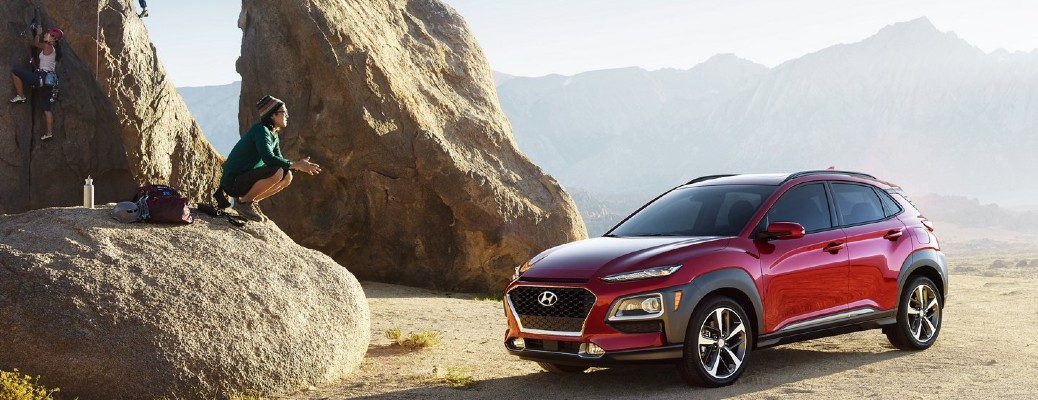 2021 Hyundai Kona red exterior front fascia driver side parked in desert people rock climbing on left