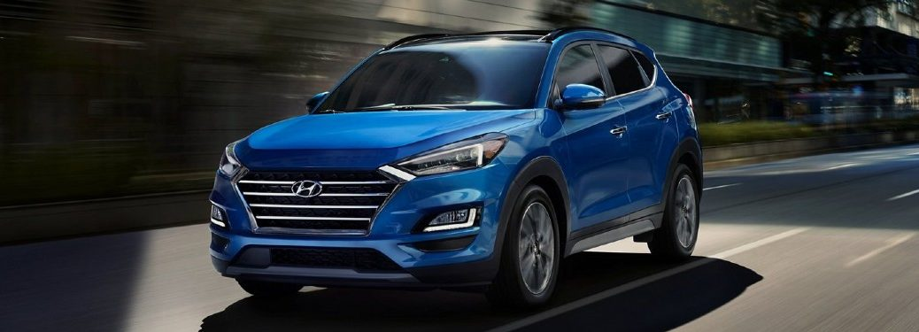 2021 Hyundai Tucson blue exterior front fascia driver side driving in city