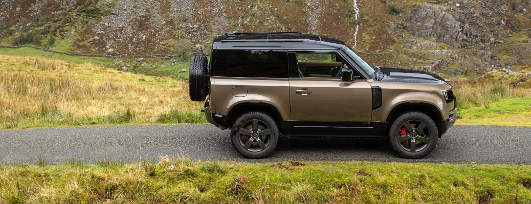 2021 Land Rover Defender exterior side shot with Gondwana Stone color option parked on a grassy mountain trail
