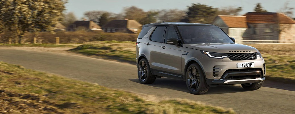 2021 Land Rover Discovery model with beige bronze paint color driving on a suburban forest road