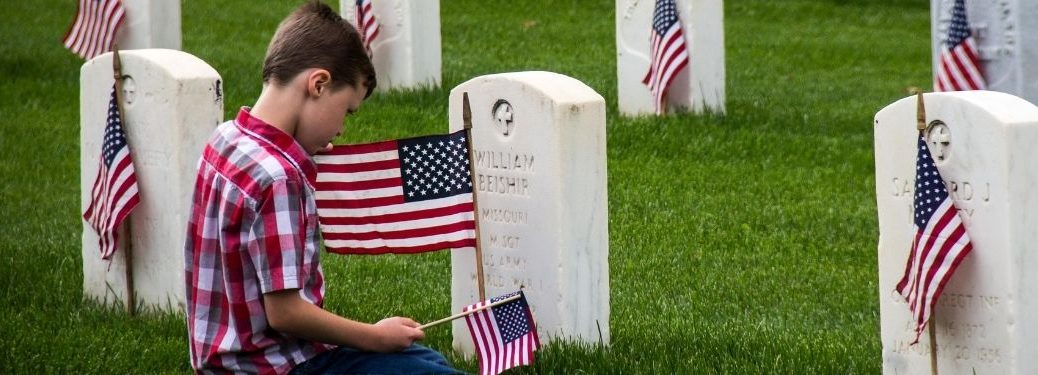 Boy Kneeling by a Military Headstone with American Flag on Memorial Day