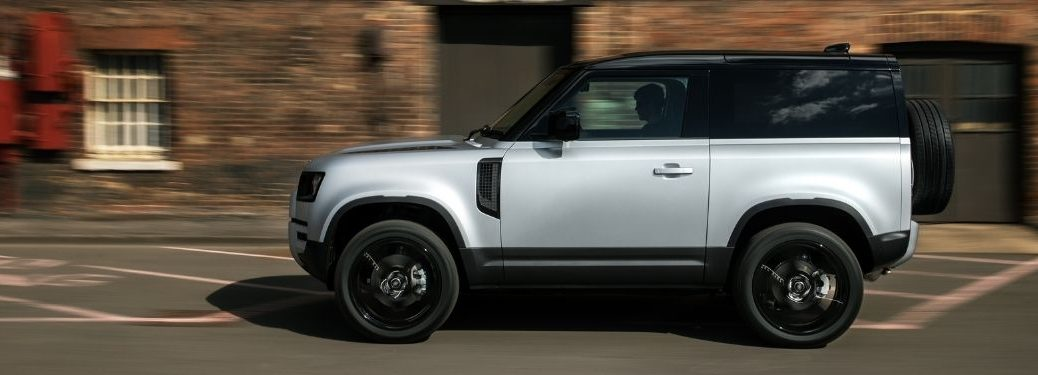 Silver 2021 Land Rover Defender Side Exterior on a City Street