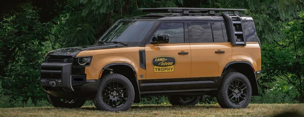 Side view of the yellow and black Land Rover Trophy Edition in a jungle
