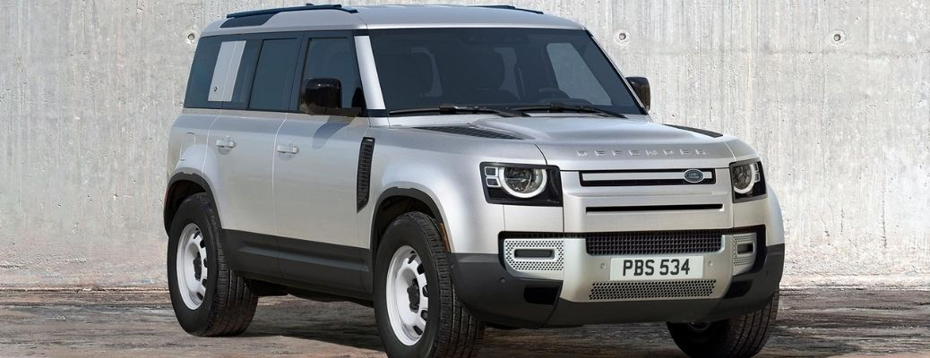 A silver-colored 2021 Land Rover Defender 110 parked in front of a wall