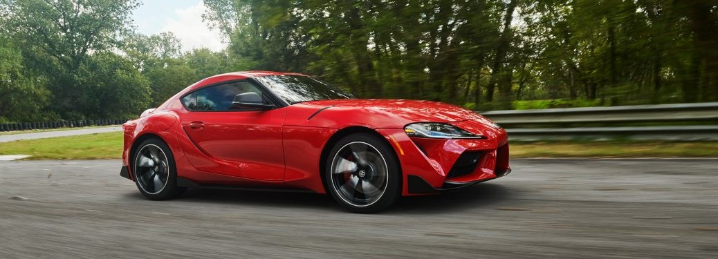 Side view of a red 2020 Toyota Supra driving on open road