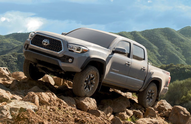 front left view of gray toyota tacoma driving on rocks and dirt