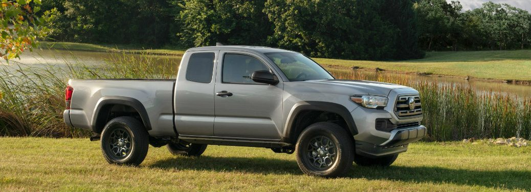 right side view of gray toyota tacoma parked on grass