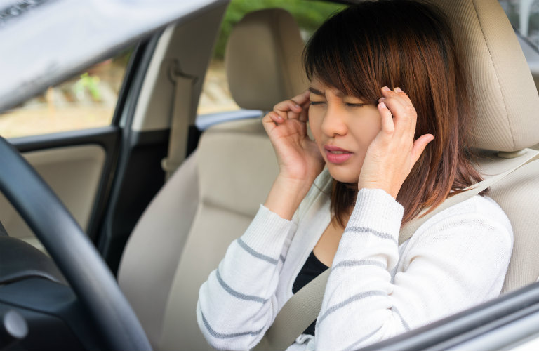 woman in car rubbing temples in pain