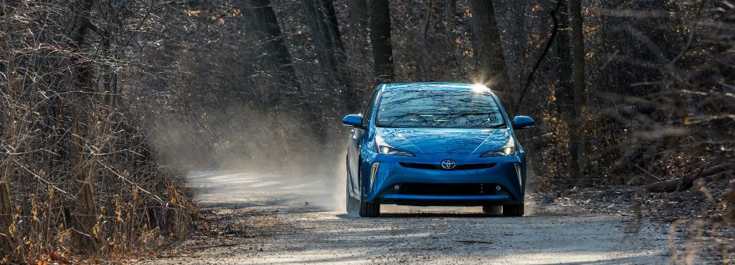 front view of blue toyota prius on wooded road