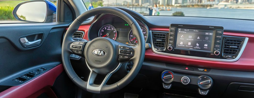 2018 Kia Rio interior front driver's seat view of steering wheel, dashboard, transmission, and cityscape background out of the windshield glass