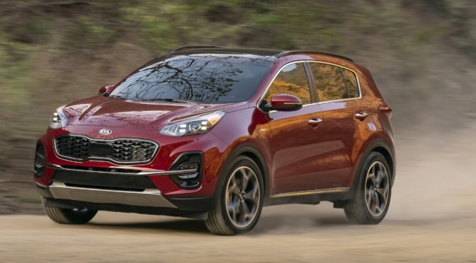 2020 Kia Sportage red side view on a sandy road