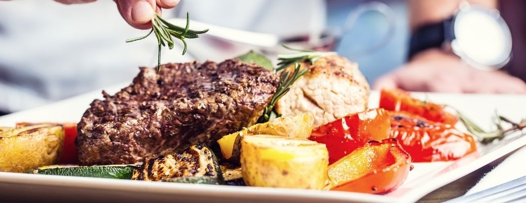 A steak served with potatoes and tomatoes