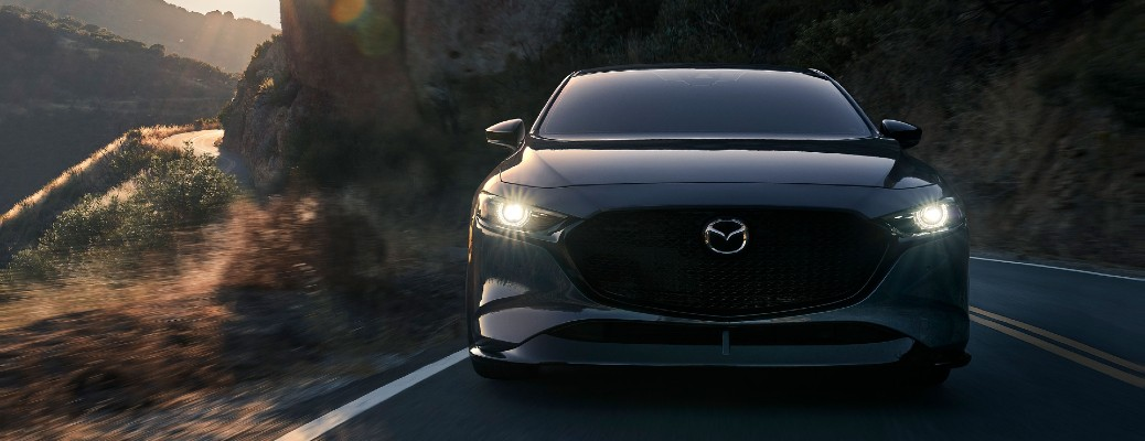 A gray 2021 mazda3 Sedan driving with its lights on.