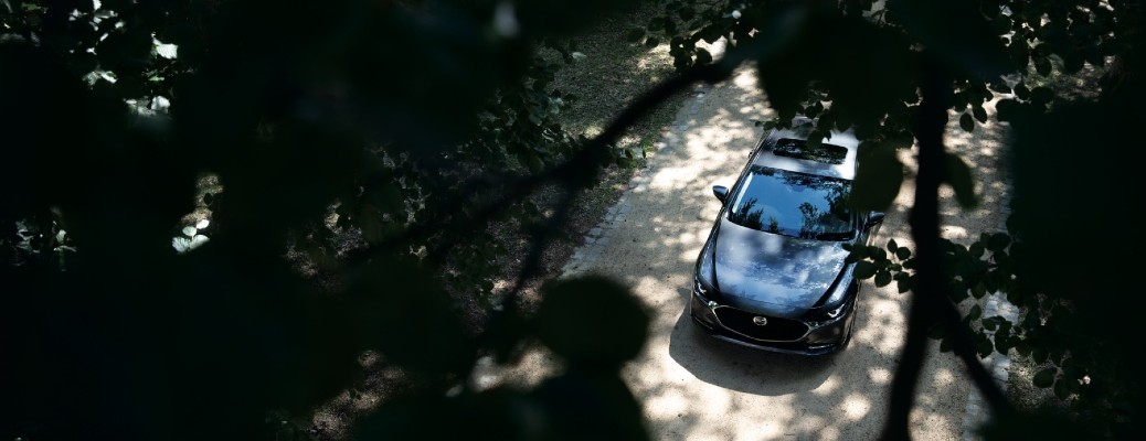 The top view of a gray 2021 Mazda3 Sedan through the trees.
