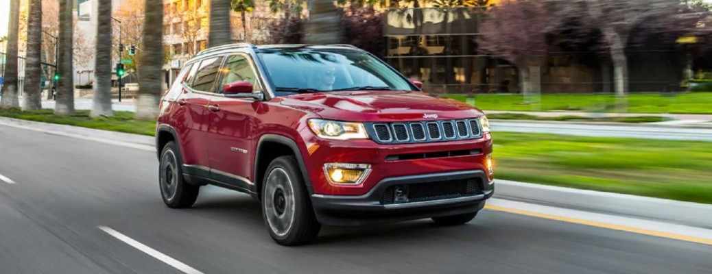A red-colored 2021 Jeep Compass driving down a road with palm trees and grass in the background