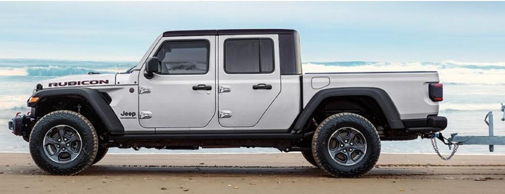 A 2021 Jeep Gladiator driving on a beach while towing something