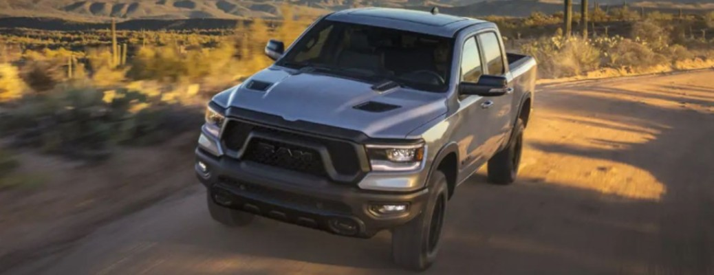 A 2021 RAM 1500 Big Horn driving on a road