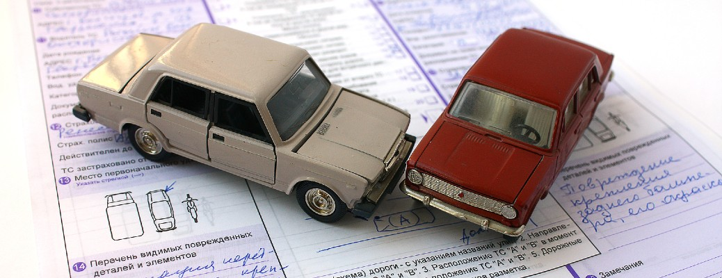 Two toy cars collided while sitting on an insurance document