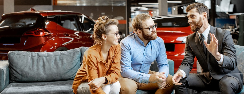 Three people talking about cars while sitting inside a dealership