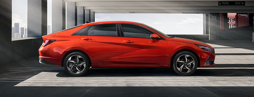 A red-colored Hyundai Elantra parked in an enclosed building with windows