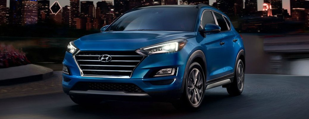 A blue-colored 2021 Hyundai Tucson driving at night with headlights on