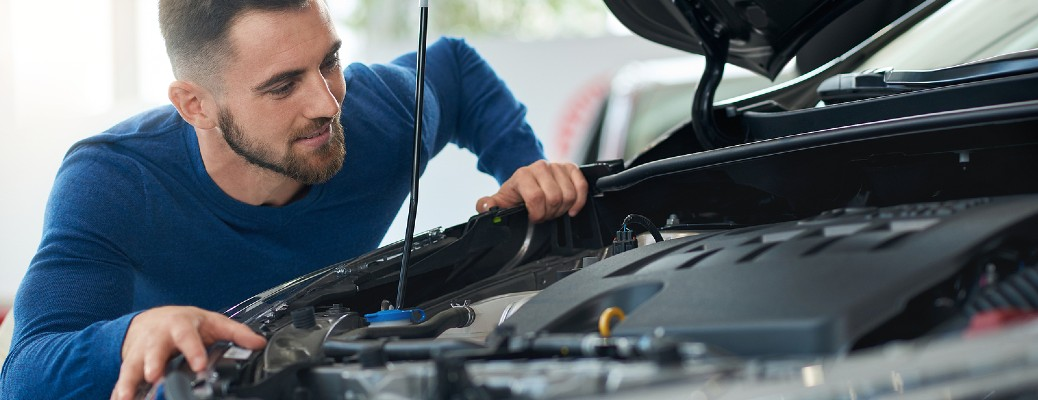 A man in a blue shirt looking under the hood of a car