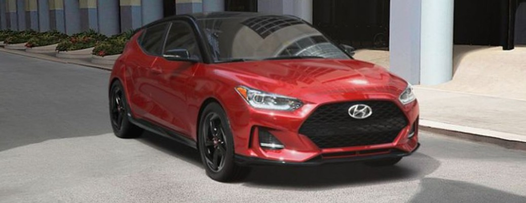 A red-colored 2021 Hyundai Veloster parked outside