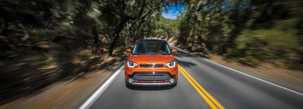 orange kia soul driving down road surrounded by trees