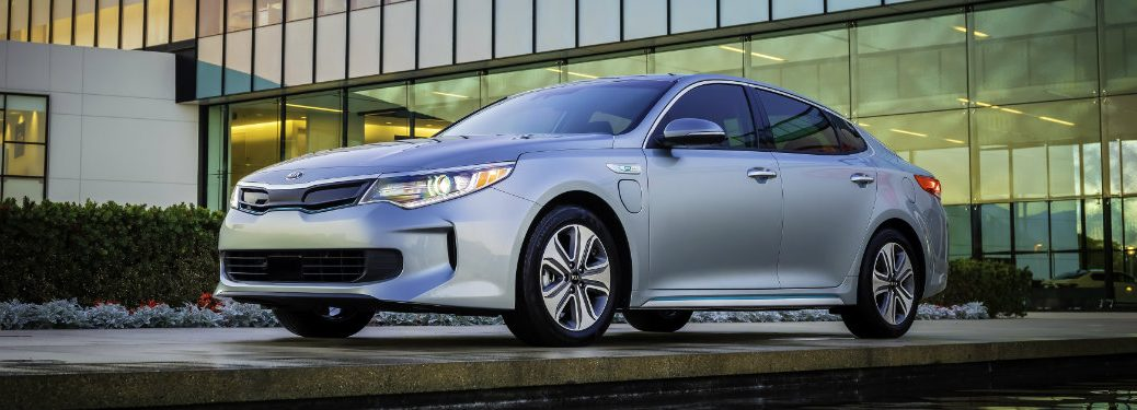 silver kia optima parked in front of glass building