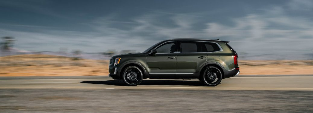 left side view of kia telluride driving on rural road