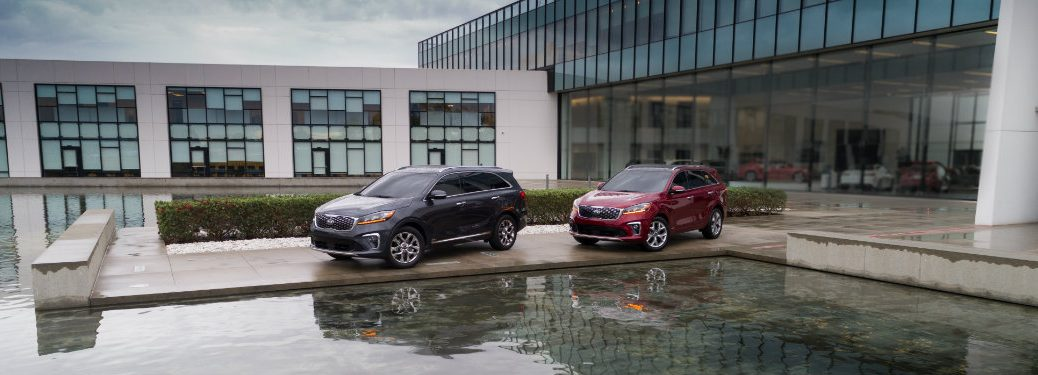 gray and red kia sorentos parked by pool outside building