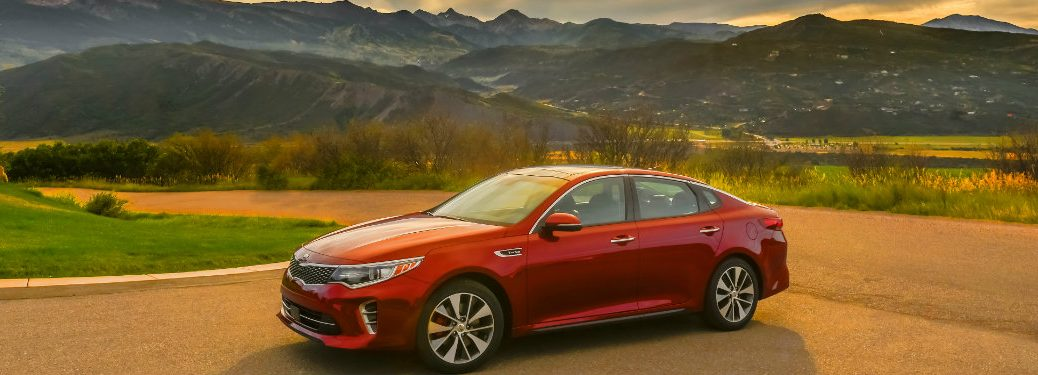 left side view of red kia optima parked in rural area