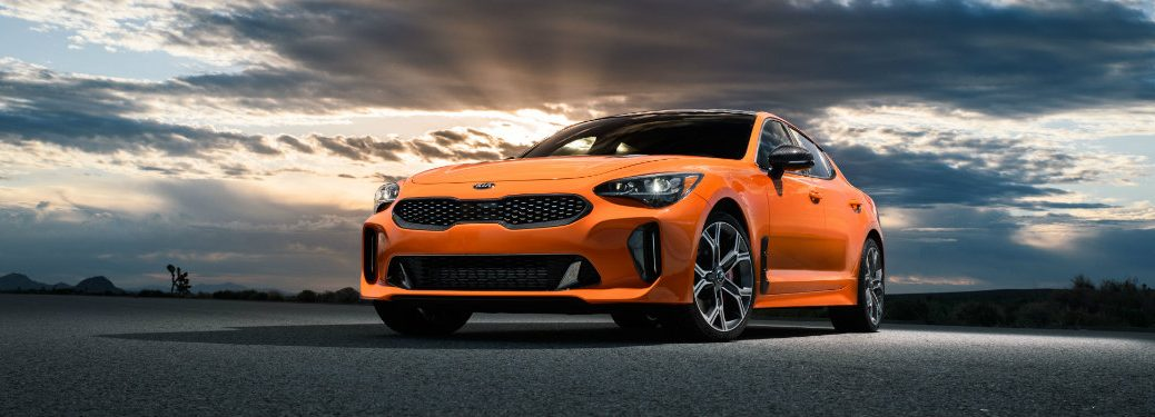 front view of parked orange kia stinger with sunset in background