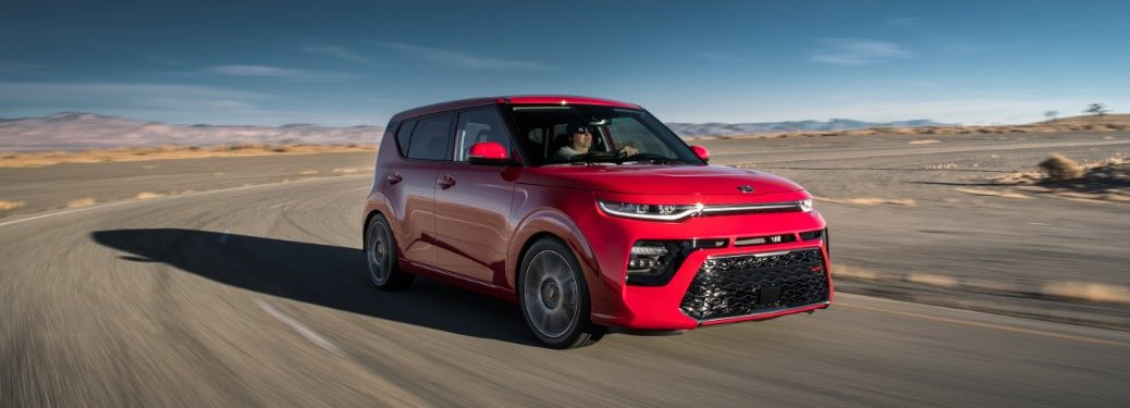 front right view of red kia soul driving