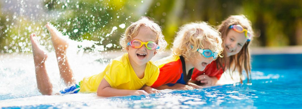 three happy kids playing in pool