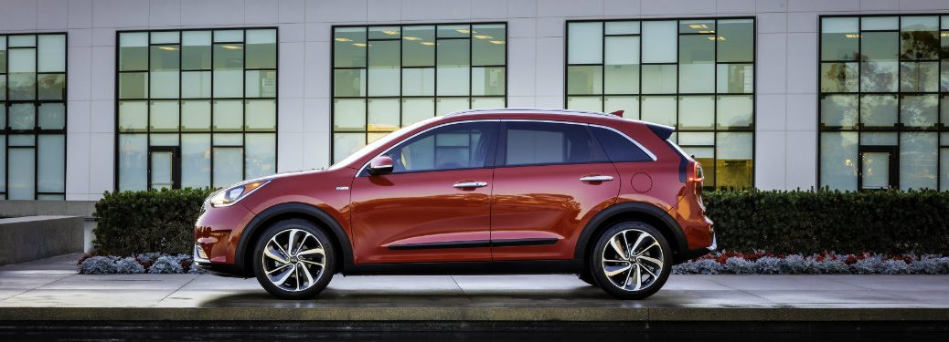 left side view of parked red kia niro