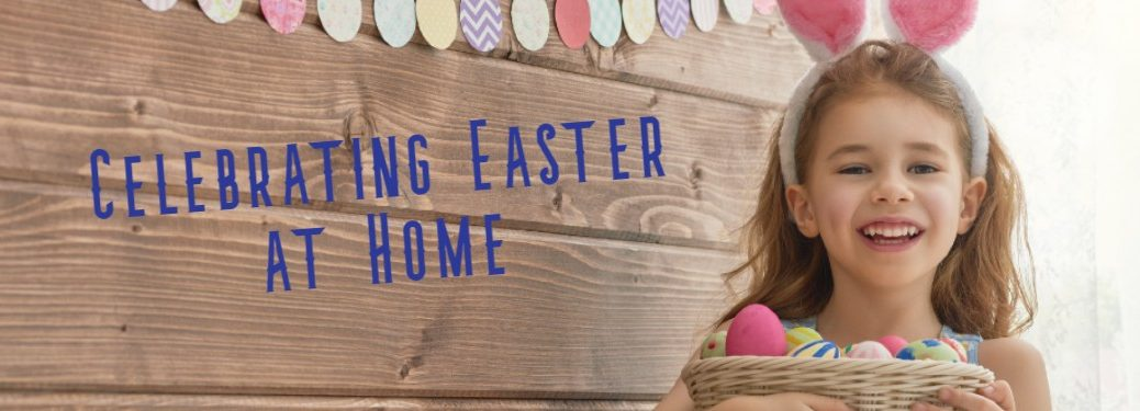 "A picture of a little girl with bunny ears indoors smiling with the caption along the wooden wall saying ""Celebrating Easter at Home""."