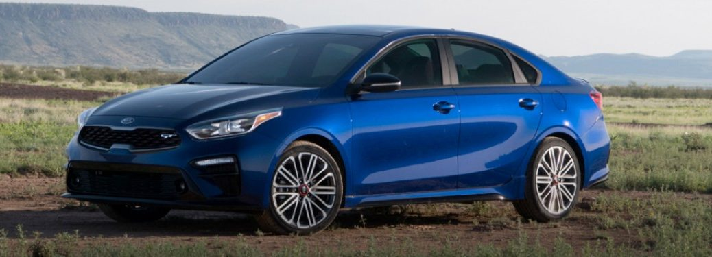 The front and side image of a blue 2020 Kia Forte parked in an open space.