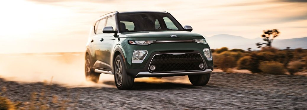 A green 2020 Kia Soul driving down a dirt road.