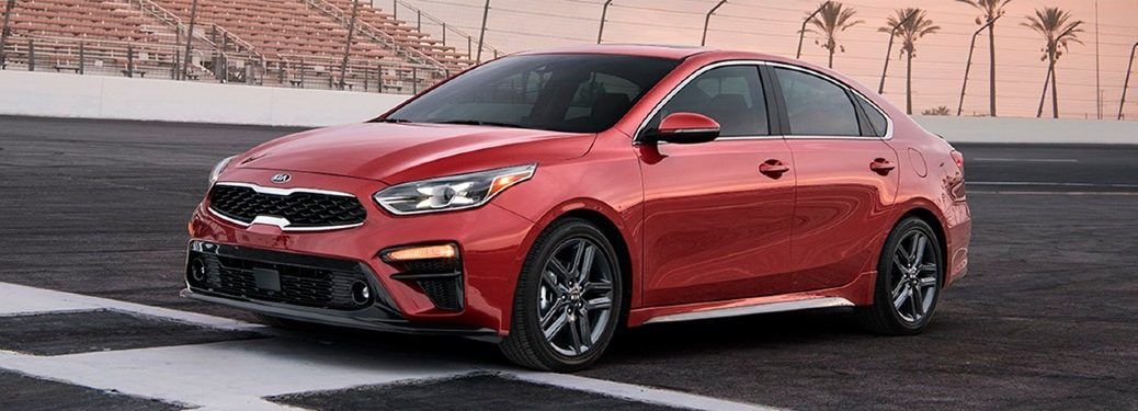 A red 2020 Kia Forte parked along a starting line on a racetrack.