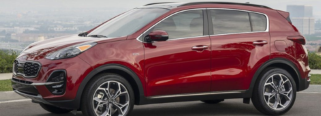 A red 2020 Kia Sportage parked along a road/