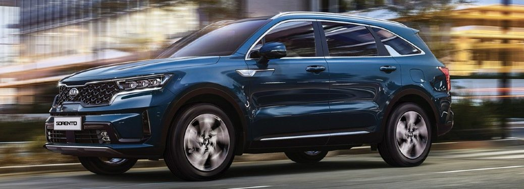 The side view of a dark blue 2021 Kia Sorento driving down a road.