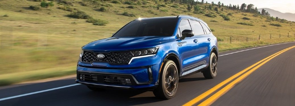 The front and side view of a blue 2021 Kia Sorento driving down a road.