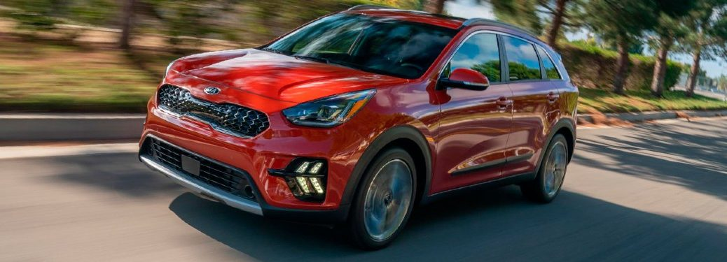The front and side view of a red 2021 Kia Niro.