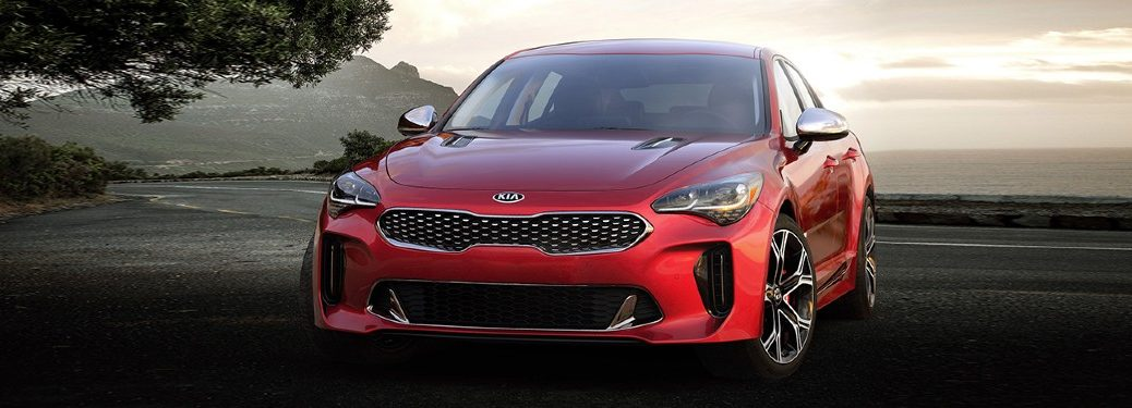 The front side of a red 2021 Kia Stinger parked on a road.