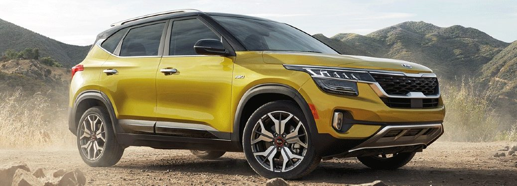 The front and side view of a yellow 2021 Kia Seltos.