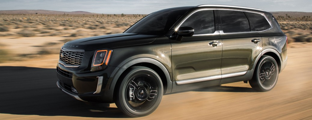 The front and side view of a dark green 2021 Kia Telluride.