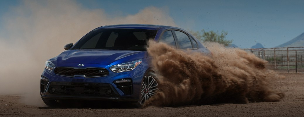 The frotn side of a blue 2021 Kia Forte blowing up sand with its tires.
